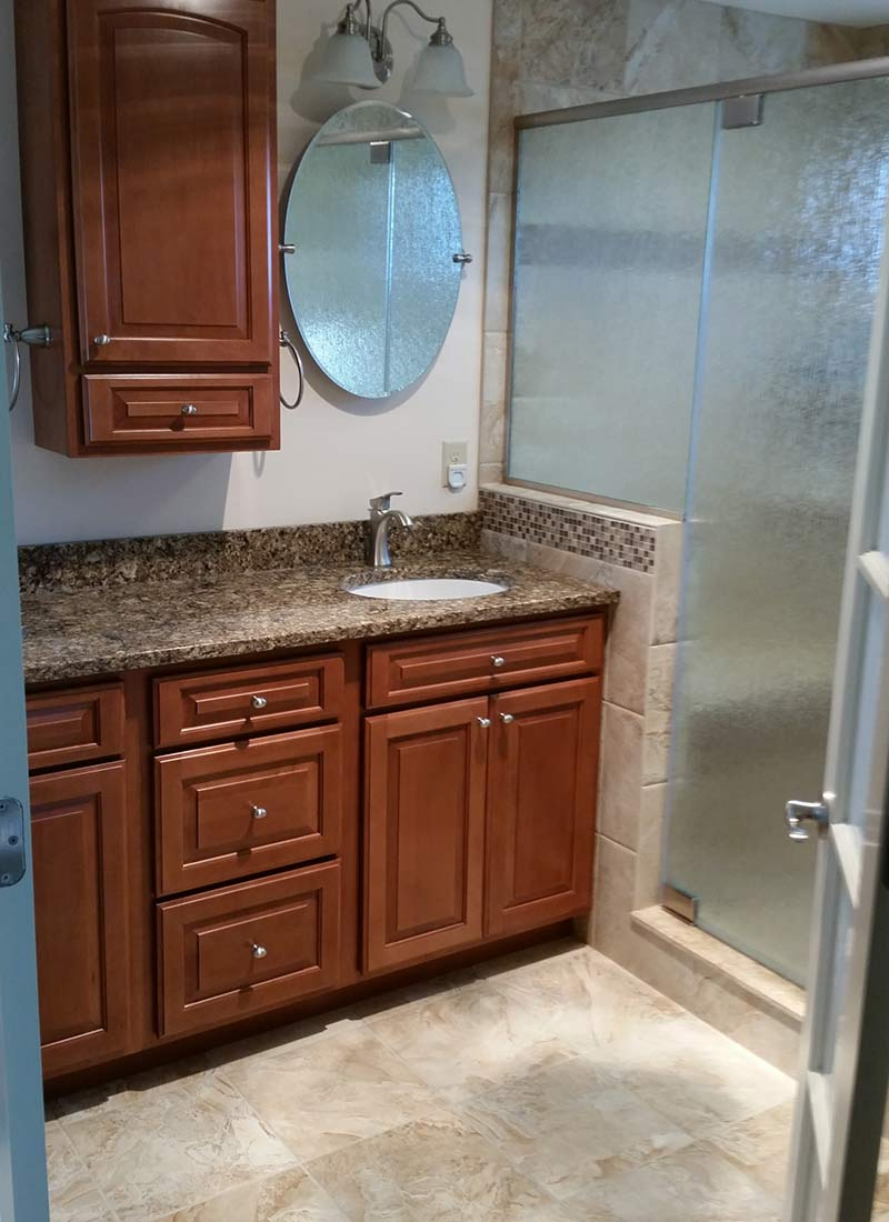 Bathroom remodel with wooden cabinets by LeFaivre Home Contractors.